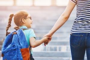 Mama vedie malú dcéru do školy