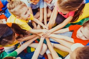 Skupinka veselých detí v kruhu, ktoré sa spoločne držia za ruky