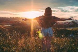 žena sa pozerá na západ slnka