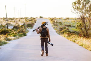 kráčajúci fotograf s fotografickou výbavou
