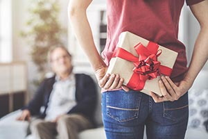 Žena, stojaca pred mužom sediacim na pohovke, pre neho za chrbtom skrýva zabalený darček s červenou mašľou