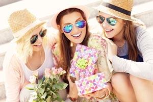 tri mladé ženy sa smejú s darčekom v ruke
