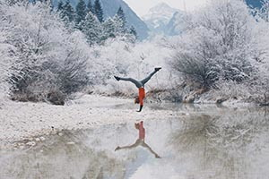 Postava ženy v diaľke robí premety v zimnej prírode pri zamrznutom jazere