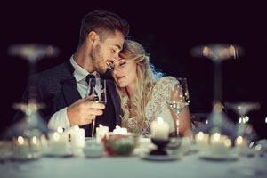 Nevesta a ženích pritúlení sa za stolom
