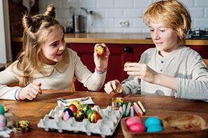 Deti sediace za kuchynským stolom zdobia veľkonočné vajíčka