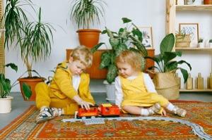 Dve deti v žltých šatách sa hrajú doma v obývačke na koberci s vláčikom